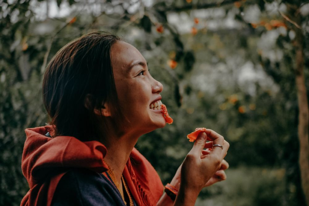 woman biting red fruit