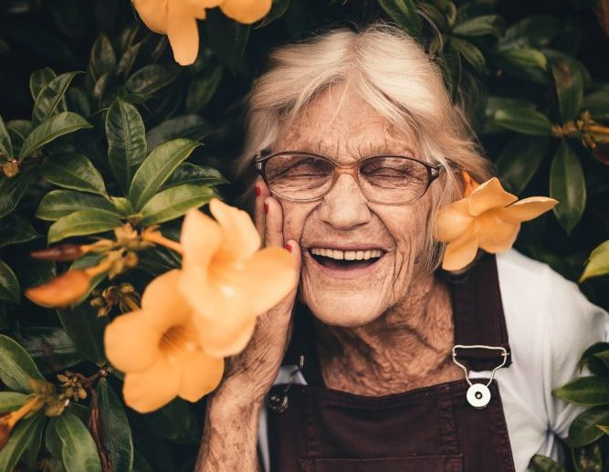 old lady standing near yellow petaled flower